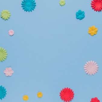 Colorful origami flowers cutout on blue background