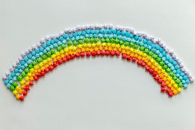 무지개 배경을 형성하는 다채로운 종이 접기 별