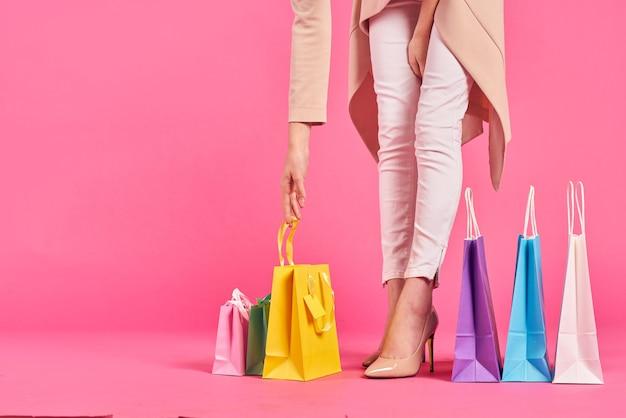 カラフルなパッケージの女性の足のピンクの壁のギフトの買い物。