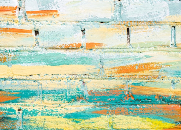 Colorful paint marks on a brick wall. abstract painting colorful background texture. pastel color. mosaic of bricks in modern style. painted rock texture. facade of building. masonry rough surface.