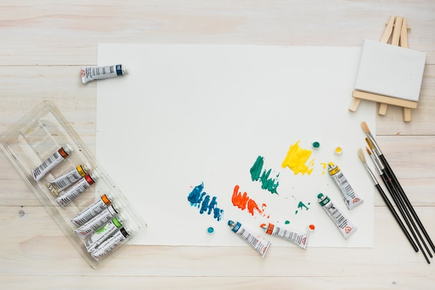 Colorful paint tube colors on white sheet with mini easel and brushes