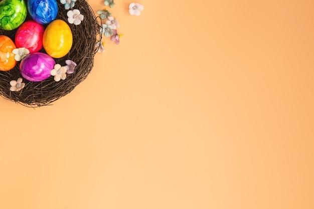 오렌지 파스텔 컬러 배경 평면도와 다채로운 그린 된 부활절 달걀 둥지