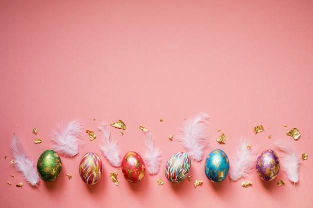 황금 호 일 및 분홍색 배경에 흰색 깃털을 가진 다채로운 페인트 부활절 달걀. 인사말 카드 디자인, 복사 공간, 디자인 또는 텍스트에 대 한 장소.