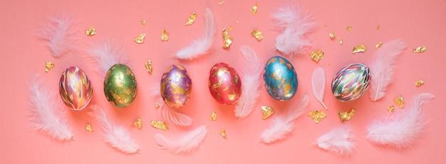 ピンクの背景に白い羽と金箔の断片でカラフルに描かれたイースターエッグ。イースターバナー。