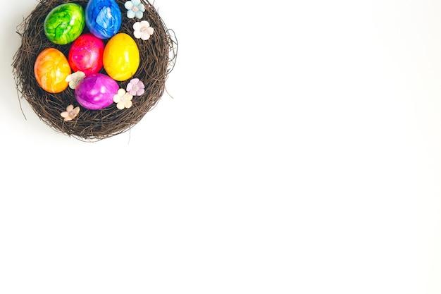 茶色の巣にカラフルなペイントされた手作りのイースターエッグ
