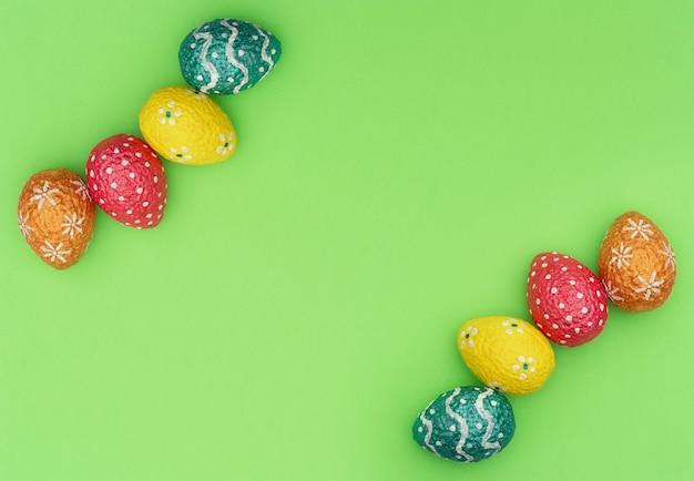 緑にカラフルに描かれたオレンジ、青、赤、黄色のイースターエッグ