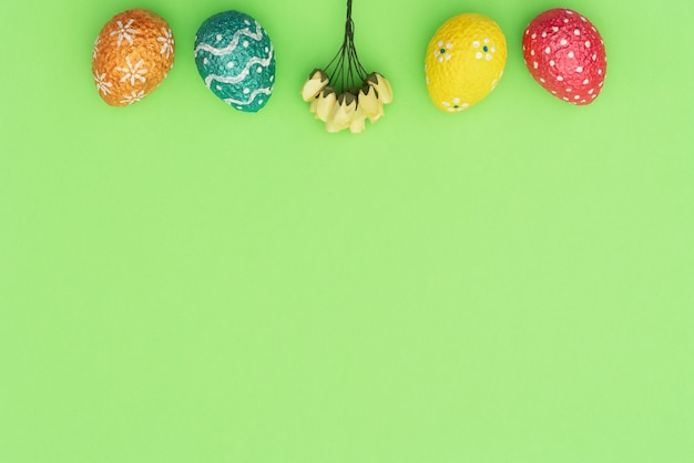 緑に黄色の春の花とカラフルな塗装オレンジ、青、赤、黄色のイースター卵