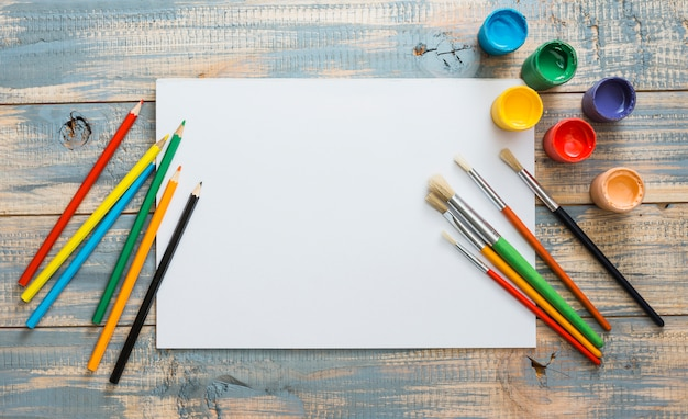 Colorful painting supplies with white blank paper over wooden background