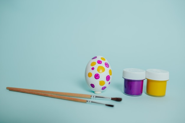 Colorful paints and brushes. easter egg painting process. dotted easter egg.
