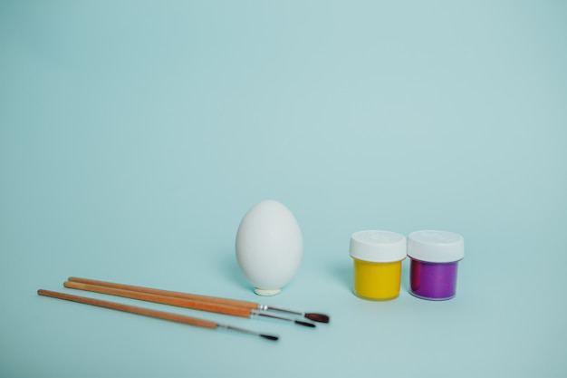 Colorful paints and brushes. easter egg painting process.
