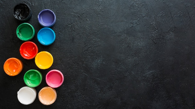 Colorful paints containers on black textured backdrop