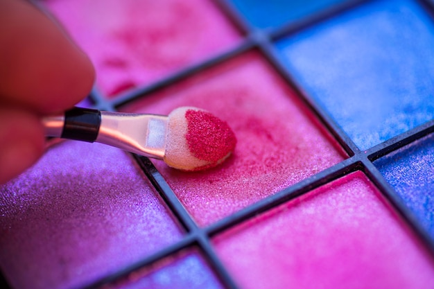 Colorful palette for makeup with hand holding brush