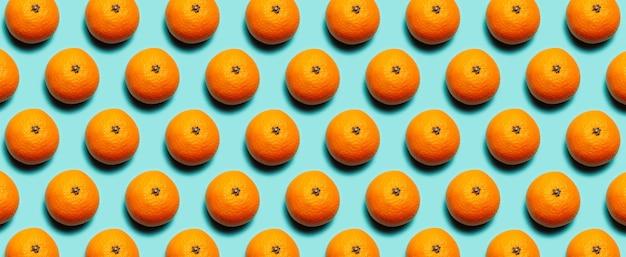 Красочный панорамный узор из свежих плодов апельсина мандаринов на фоне голубого или бирюзового цвета.