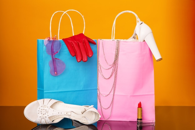 Colorful paper bags with sandals, glasses, red gloves, necklace and cosmetics on a black glass table and a yellow