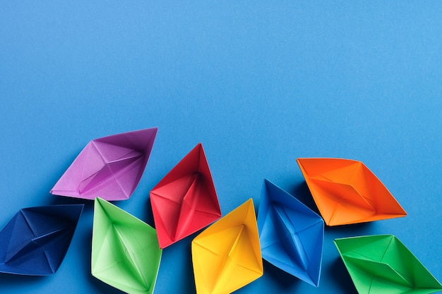 Colorful paper boats on a bright blue background. copy space