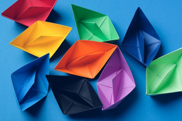 Colorful paper boats on a bright blue surface. copy space
