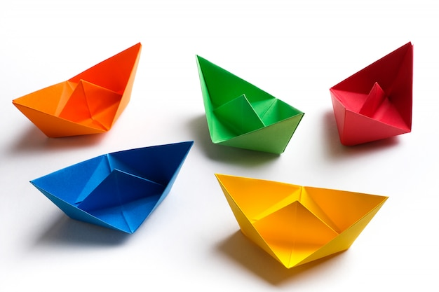 Colorful paper boats on a bright surface. copy space