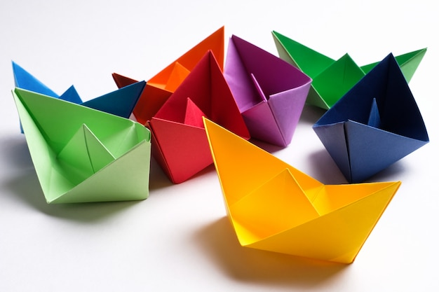 Colorful paper boats on a bright white surface. copy space