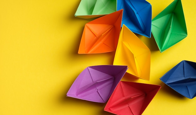 Colorful paper boats on a bright yellow background. copy space