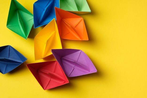 Colorful paper boats on a bright yellow surface. copy space