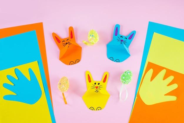 화려한 배경에 어린이 손 손바닥에서 다채로운 종이 토끼