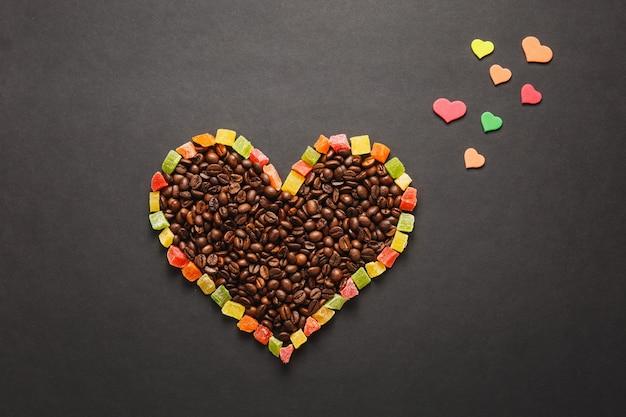 カラフルな紙、ハートの形の砂糖漬けの果物、デザインのために黒い背景に分離された茶色のコーヒー豆。聖バレンタインデーカード、2月14日、休日のコンセプト。広告用のスペースをコピーします。