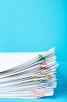 青に過負荷の白い書類の山でカラフルなペーパークリップ