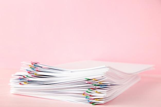 ピンクのオーバーロードの白い書類の山でカラフルなペーパークリップ