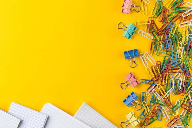 Colorful paper clips and binder clips on yellow background, copy space