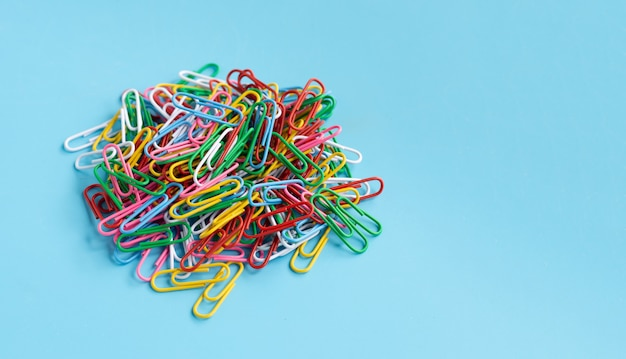 Colorful paper clips on blue background.