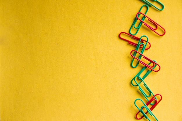 노란색 배경에 고립 된 다채로운 종이 클립