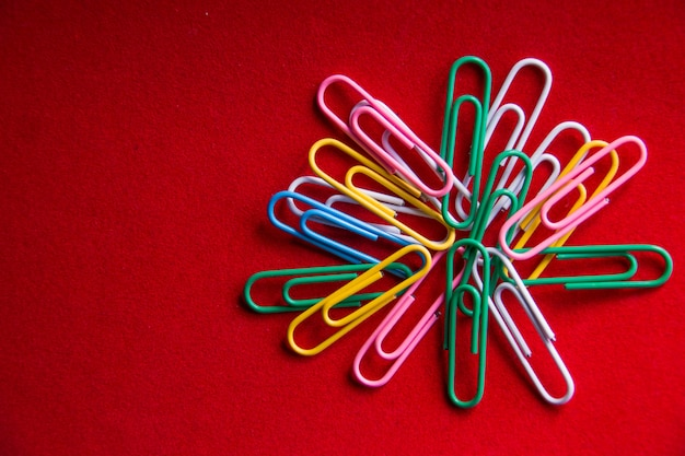 Colorful paper clips isolated on red background
