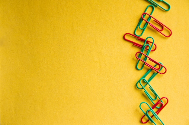 Colorful paper clips isolated on yellow background