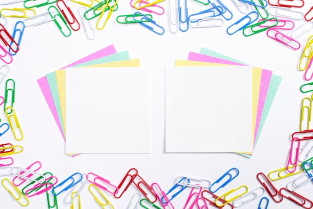 Colorful paper clips and note papers in the centre of composition isolated on white.