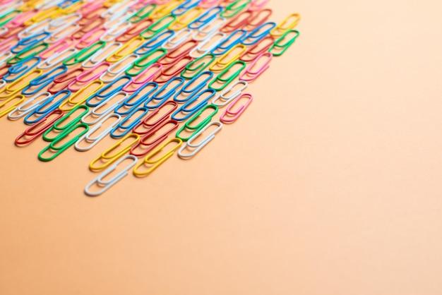 Красочные скрепки на оранжевом фоне. обратно в школу. разноцветные проволочные заглушки являются одним из видов офисного материала. copyspace