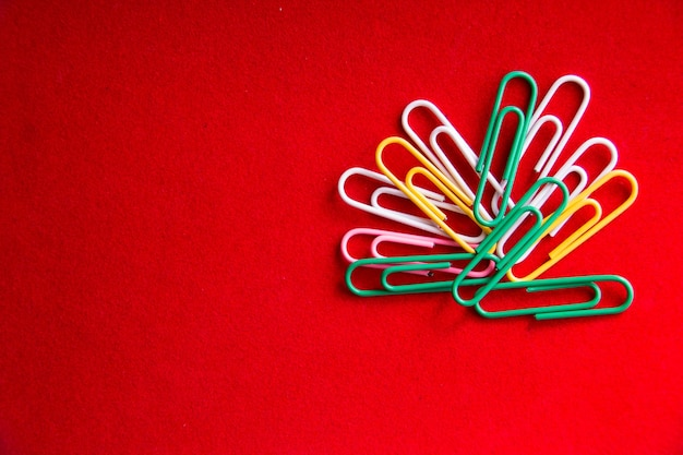 Colorful paper clips on red table