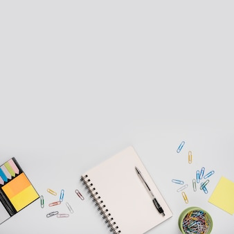 Цветные скрепки; спиральный ноутбук с ручкой и клейкие заметки на белом фоне