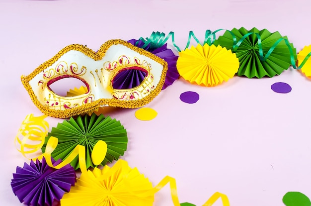 Красочное бумажное конфетти, карнавальная маска и цветной серпантин на розовом фоне с копией пространства, поздравительная открытка и дизайн шаблона приглашения на вечеринку для карнавала или дня рождения, марди гра,