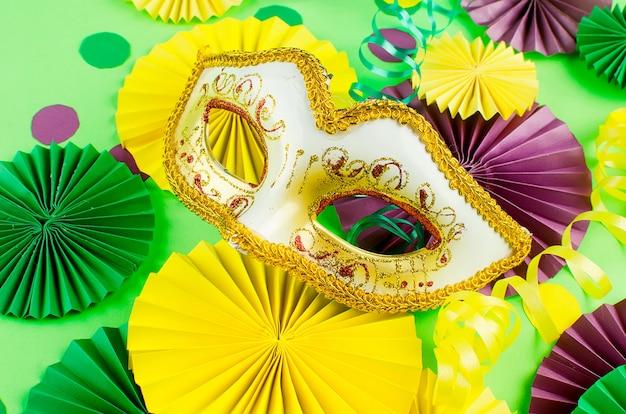 Красочное бумажное конфетти, карнавальная маска и цветной серпантин на желтом фоне