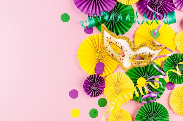 Colorful paper confetti, carnivale mask and colored serpentine on a pink background
