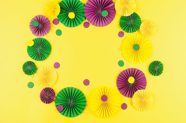 Colorful paper confetti, carnivale mask and colored serpentine on a yellow background