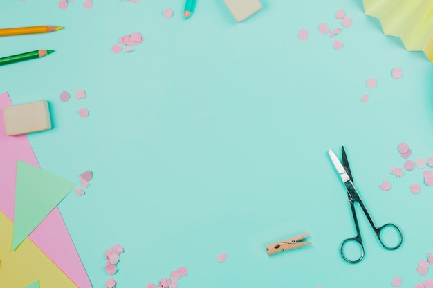Colorful paper; confetti; colored pencils; clothespin and scissor on teal background