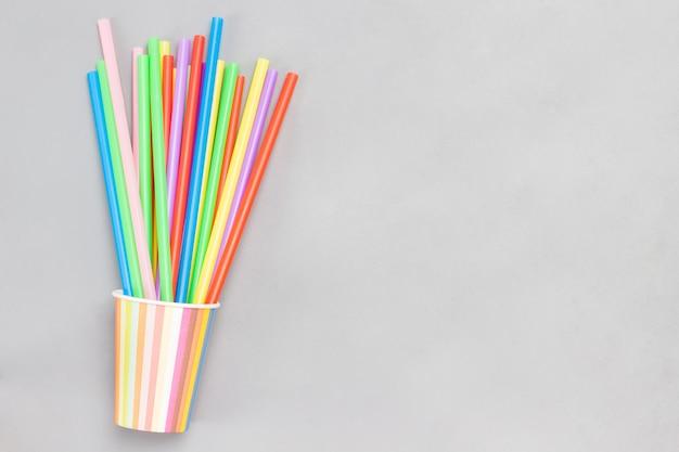 Разноцветные бумажные стаканчики и разноцветные пластиковые соломинки для напитков