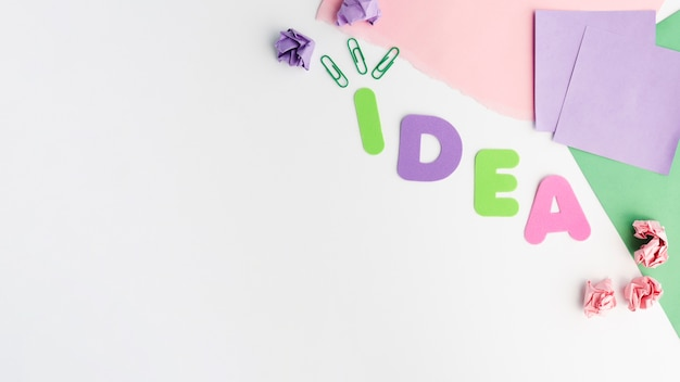 Colorful paper cutout of idea text letter and paperclip with crumpled paper