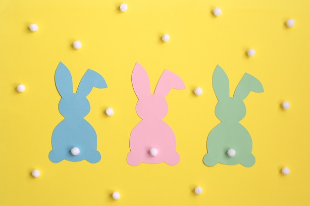 Colorful paper easter bunnies on yellow background, decorated with fluffy balls