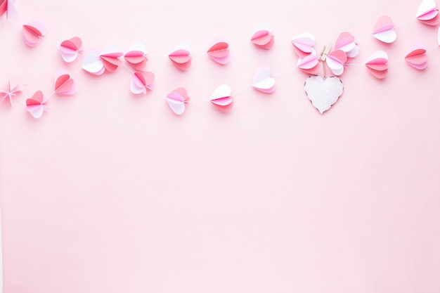 Colorful paper garland of hearts on the living coral background. valentine day greeting cards.