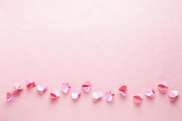 生きている珊瑚の背景にハートのカラフルな紙の花輪。バレンタインデーのグリーティングカード。