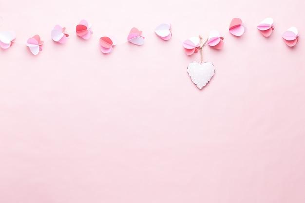 Красочная бумажная гирлянда из сердечек на фоне живых кораллов. поздравительные открытки ко дню святого валентина.