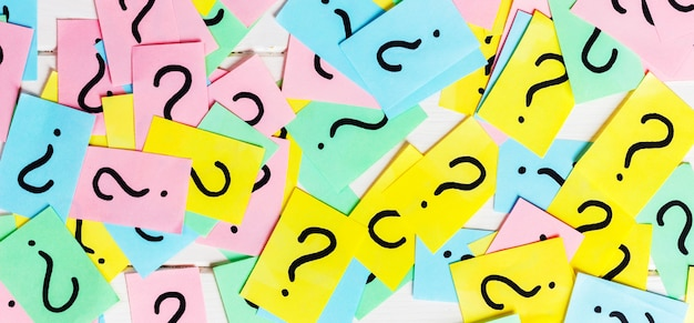 Colorful paper notes with question marks. closeup Premium Photo