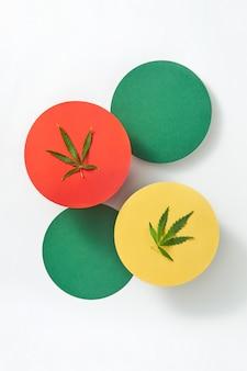 ライトグレーのテーブル、コピースペースに天然医療大麻の葉が付いたカラフルな紙の丸いカード。医療目的での大麻の使用。上面図。